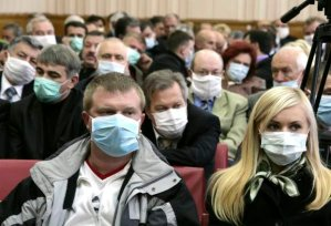 The participants of the Ministers' Cabinet session wear masks as they listen to Ukraine's Prime Minister Yulia Tymoshenko in Ternopil in western Ukraine October 30, 2009. Ukraine closed schools and banned public meetings including election rallies and restricted travel on Friday for a three-week period after confirming its first death from H1N1 flu.  REUTERS/Viktor Gurniak  (UKRAINE HEALTH POLITICS)